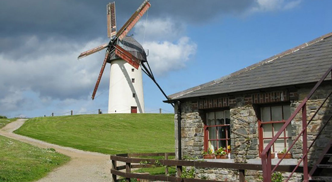 Skerries windmill on top of grass hill with stone building in foreground